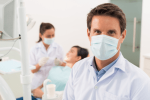 dentist wearing mask in foreground, dental assistant working with patient in background